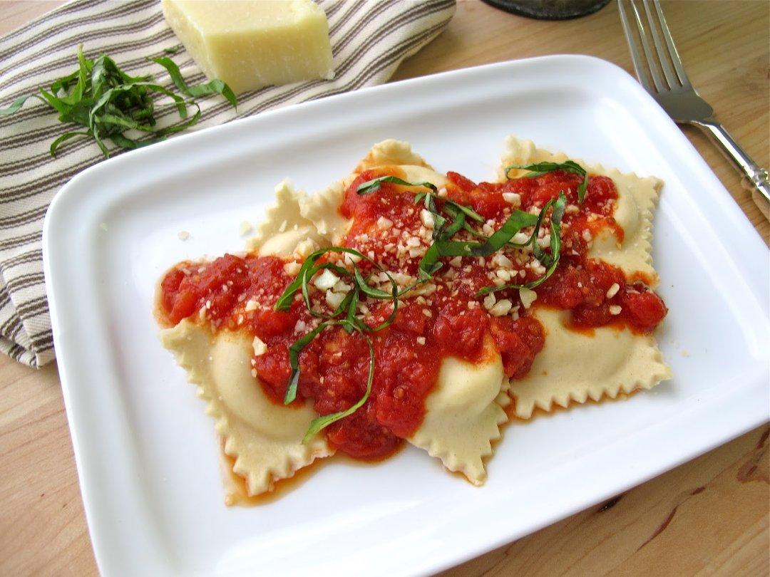 Готовые равиоли с рикоттой и соусом из томатов на белой прямоугольной керамической тарелке