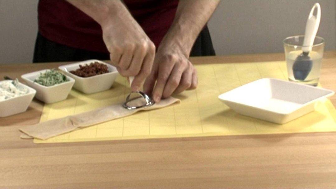 Формирование и вырезка равиоли на поверхности для теста с помощью ручного штампа-пресса от Tescoma